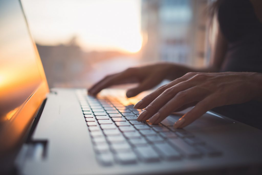 Woman working at home office hand on keyboard close up